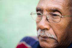 Worried senior african american man with eyeglasses Stock Photos