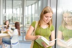 high school student read book by window - stock photo