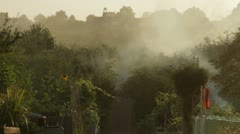 Smoke burning allotments wide Stock Footage