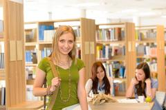smiling student girl leaving library high school - stock photo
