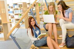 group of high school classmates study library - stock photo
