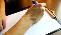Writing a business letter, white piece of paper on wooden desk in the office - stock footage