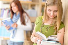Teenage student read book at high school library Stock Photos