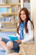 Happy student with notepad at high-school library Stock Photos