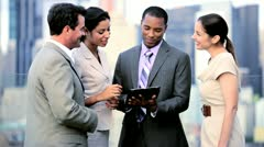 Multi ethnic management discussing data online on tablet on rooftop city office  Stock Footage