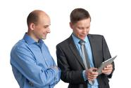 Stock Photo of businessmen meeting and looking at tablet computer