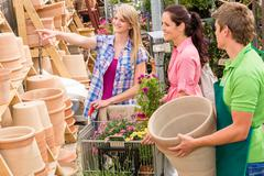 Garden center salesman selling pot to customer Stock Photos