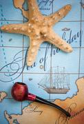 Tobacco pipe and  starfish on map Stock Photos