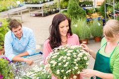 Florist assist woman choose flowers garden store Stock Photos