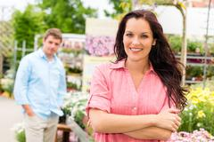 smiling woman standing at garden center - stock photo
