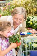 garden center girl with grandmother smell flower - stock photo