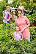 mother daughter shopping flowers in garden center - stock photo
