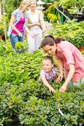 Stock Photo of mother daughter choosing flowers at garden center