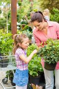 Stock Photo of mother daughter choosing flowers in garden shop
