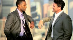 African American and Caucasian businessmen discussing commodities on rooftop   Stock Footage