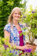 woman hold tree plant at garden center - stock photo
