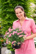Smiling woman hold pink potted flower Stock Photos