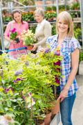 smiling woman at garden center shopping plants - stock photo
