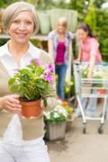 senior woman hold potted flower garden shop - stock photo