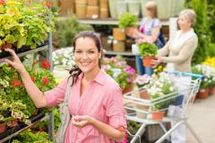 woman buying potted flower in garden shop - stock photo