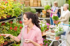 woman choose potted flower in garden store - stock photo
