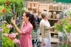 woman taking potted plant at garden center - stock photo