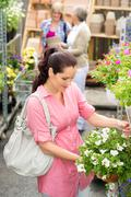 garden centre woman hold white surfinia flower - stock photo