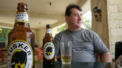 MAN ENJOYING A TUSKER BEER Kenya, Africa Stock Footage