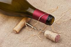 wine bottle and corkscrew on a canvas - stock photo