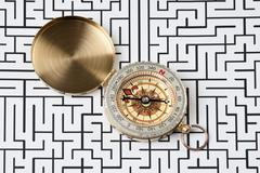 compass on background of the labyrinth - stock photo