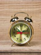 golden alarm clock  on  wooden table - stock photo