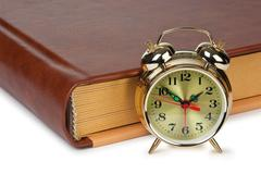 golden alarm clock on the book  isolated - stock photo