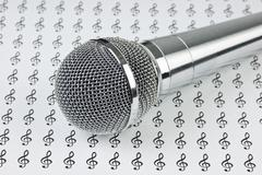 Microphone on background of the treble clef Stock Photos