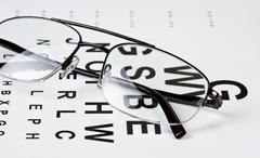 glasses on eyesight test chart - stock photo