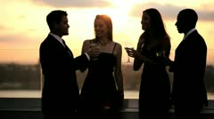 Multi ethnic men and women dating at cocktail roof party dressed in black   Stock Footage