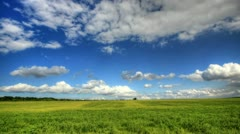 Timelapse clouds over the green field. Stock Footage