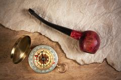 compass and a tobacco pipe on a wooden board - stock photo