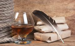 quill in the inkwell and glass of wine - stock photo