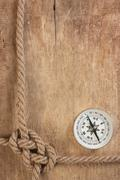 compass and rope knot on wooden background - stock photo