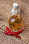 Red chili peppers and a bottle of spiced Stock Photos
