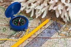 compass and coral on map - stock photo
