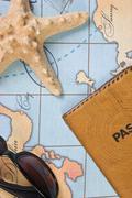Stock Photo of passport and sunglasses on map