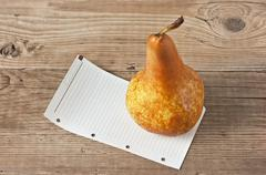 pear and a note  on a wooden background - stock photo
