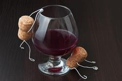 figures from wine corks and a glass of wine - stock photo