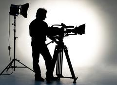 Searchlight and silhouette of the camera and cameraman. Stock Photos