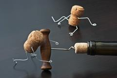 Two wine corks and bottle with corkscrew Stock Photos