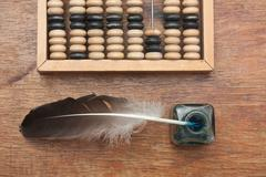 old glass inkwell with a quill pen and abacus on wooden table - stock photo
