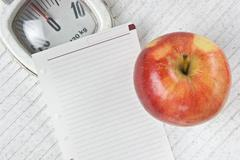apple and a note on floor scales - stock photo