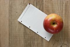 apple and a note  on a wooden background - stock photo