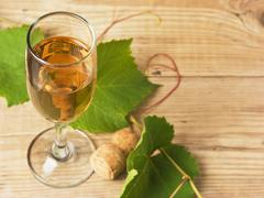 Stock Photo of glass of wine and vine on  wooden table